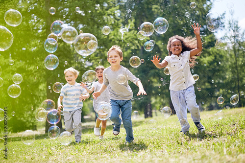 Multi-ethnic group of little friends with toothy smiles on their faces enjoying warm sunny day while participating in soap bubbles show