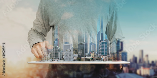 Fotografía a man using digital tablet, and modern buildings hologram