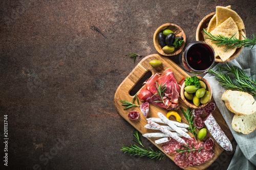 Fotografia Antipasto - sliced meat, ham, salami, olives and glass wine