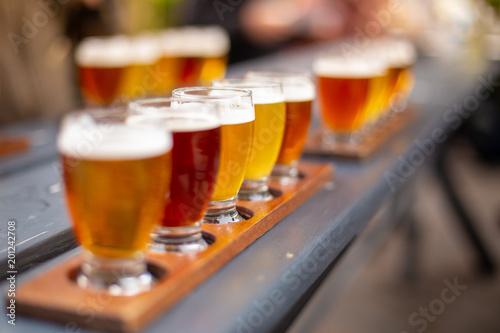 Fotografie, Obraz Line of beers on wooden table in a beer garden