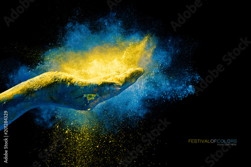 Hand holding yellow holi powder over an explosion of color
