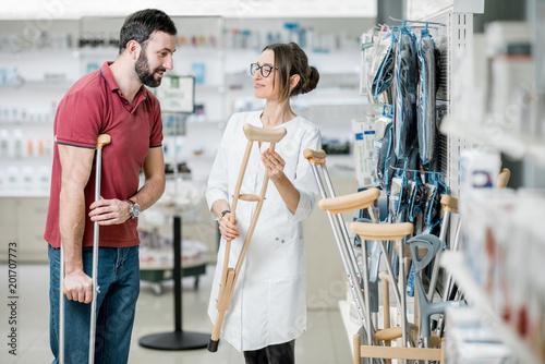 Man choosing crutches in the pharmacy Fototapeta