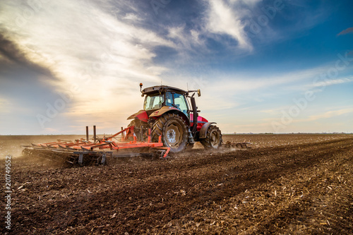 Obraz na plátně Tractor cultivating field at spring