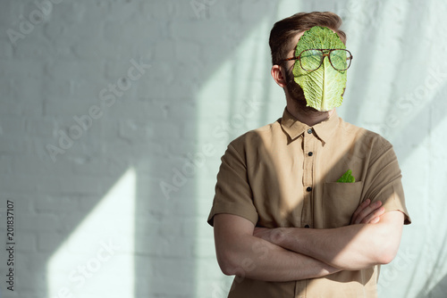 Obraz na płótnie obscured view of man with savoy cabbage leaf and eyeglasses on face, vegan lifes