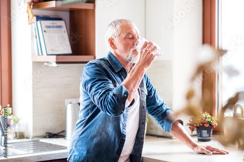 Tableau sur Toile Senior man drinking water in the kitchen.