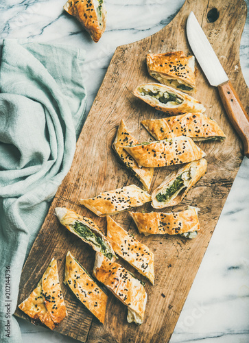 Flat-lay of fresh Turkish borek roll with spinach, feta cheese, black cumin seeds cut in slices on rustic wooden board over grey marble background, top view. Traditional East Mediterranean cuisine