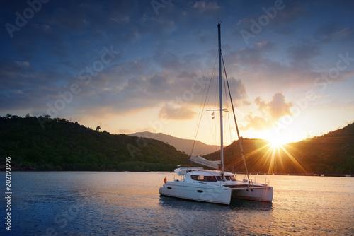 Fotografia Yacht - Catamaran in the tropical sea at sunset