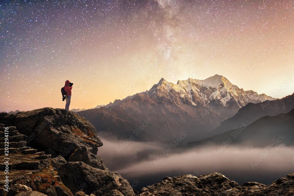 Fotograf podróżnik, który robi zdjęcie gwiaździste niebo i wschód słońca w górach <span>plik: #202294176 | autor: soft_light</span>