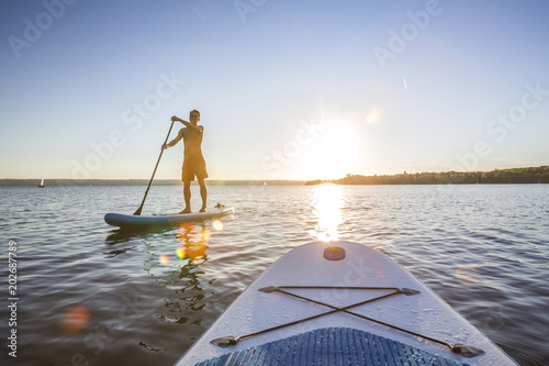Standup paddler im Sonnenuntergang Poster Mural XXL