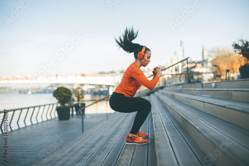 Woman with headphone exercising by river