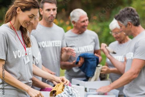 Billede på lærred Happy volunteer looking at donation box