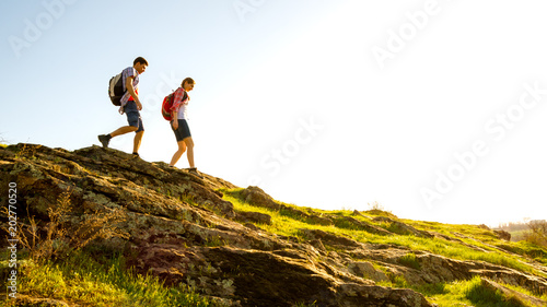 фотография Young Happy Couple Hiking with Backpacks on the Beautiful Rocky Trail at Sunny Evening
