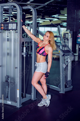 Mature woman working out with dumbbells and other program in gym. Happy middle aged woman doing exercise and training her body. Concept of healthy life
