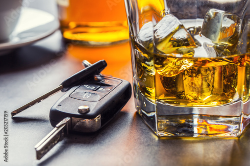 Car keys and glass of alcohol on table.