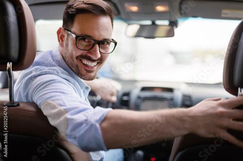 Portrait of a handsome businessman driving car