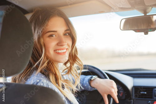 Close up portrait of pleasant looking female with glad positive expression, being satisfied with unforgettable journey by car, sits on driver`s seat, enjoys music Fototapeta
