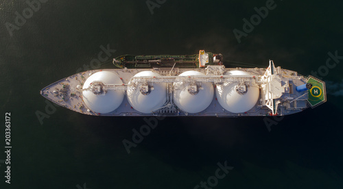 A top view of a small tanker on a roadstead unloads a large LNG tanker.