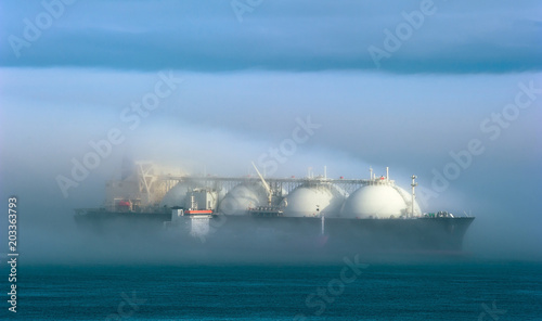 A small tanker on the roads unloads a large LNG tanker in the fog.