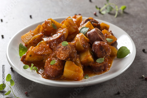 Potatoes stew with pork sausage slices and tomato sauce on a white plate