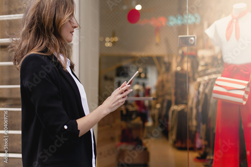 Fotografia Young beautiful woman walking along the street using smartphone and doing online
