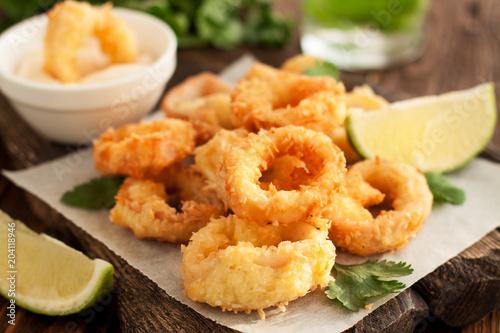 Fried calamari rings on wooden cutting board