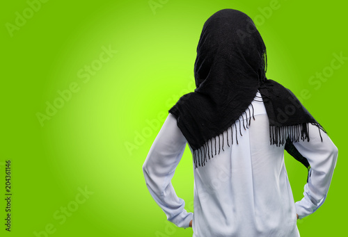 Young arab woman wearing hijab backside, rear view