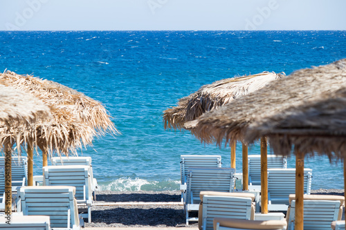 beach with umbrellas and deck chairs by the sea in Santorini Poster Mural XXL