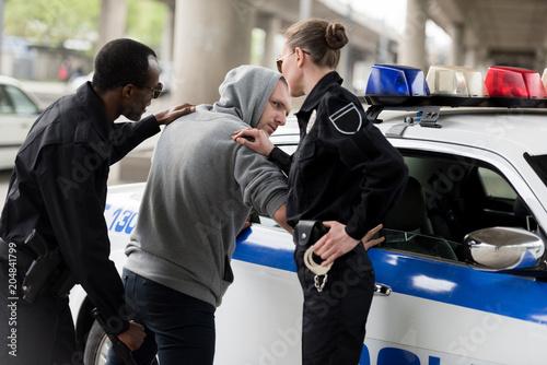 Fotografía policeman and policewoman arresting young man in hoodie
