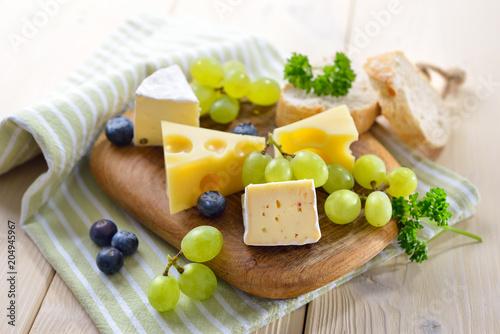 Käseimbiss mit verschiedenen Sorten auf einem Holzteller mit Baguette und Trauben serviert – Cheese snack with serveral kinds, served with bread and grapes on wooden cutting board