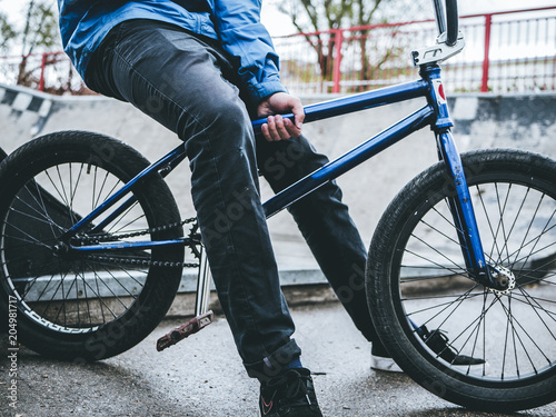 close up legs of teenager sitting in the bmx bicycle