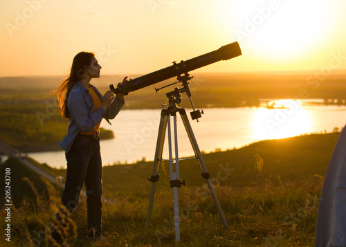 Canvas Print Silhouette of young woman looking view through the telescope at summer sunset