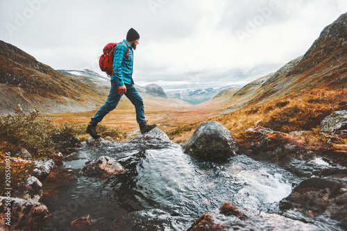 Fotografia Man solo traveling backpacker hiking in scandinavian mountains active healthy li