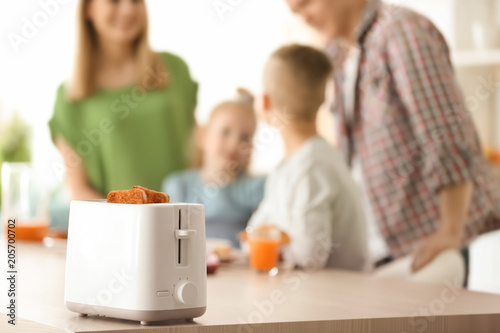 Preparing bread in toaster and blurred family on background