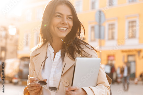 Happy brunette woman in jacket holding laptop computer