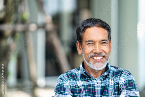 Canvas Print Portrait of happy mature man with white, grey stylish short beard looking at camera outdoor