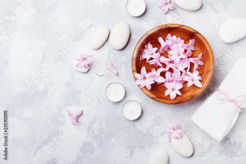 Aromatherapy, spa, beauty background with massage pebble, perfumed flowers water and candles on stone table from above. Relaxation and zen like concept. Flat lay style.