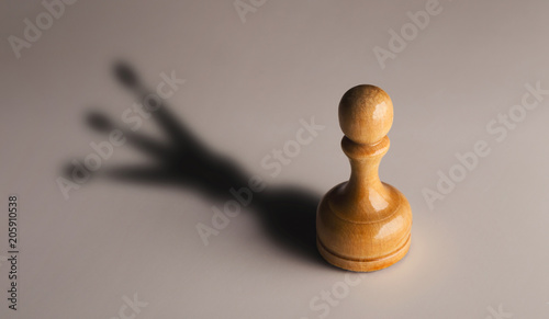 Fotografiet Wooden chess pawn with king shadow