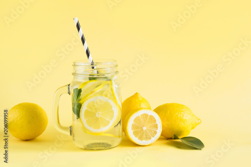 Tablou Canvas Fresh summer fruits water or lemonade with lemon and mint on yellow background