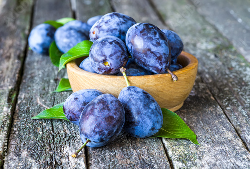 Fresh plums on wooden table background. Half of blue plum fruit. Many beautiful plums with leaves.Harvest. Autumn harvest.