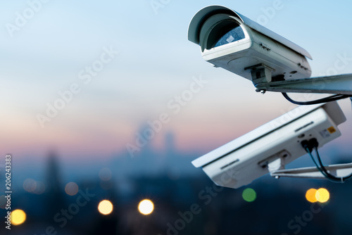 security CCTV camera monitoring system with panoramic view of a city on blurry background