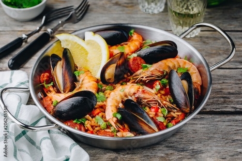 Spanish seafood paella with mussels, shrimps and chorizo sausages in traditional pan