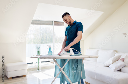 Fototapeta housework and household concept - man ironing shirt on iron board at home