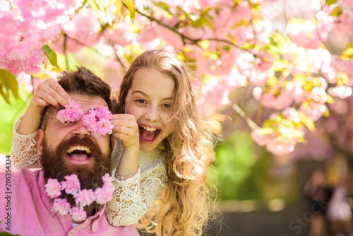 Child and man with tender pink flowers in beard. Girl with dad near sakura flowers on spring day. Father and daughter on happy face play with flowers as glasses, sakura background. Family time concept
