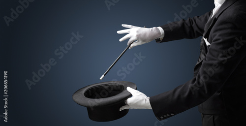 Fotografia Illusionist white hand wants to conjure with magic wand from a black cylinder so
