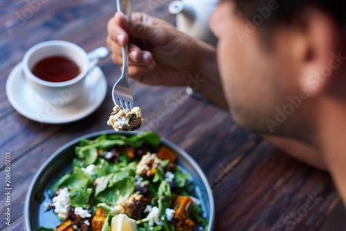 Canvas Print Man eating delicious salad while sitting at a bistro table