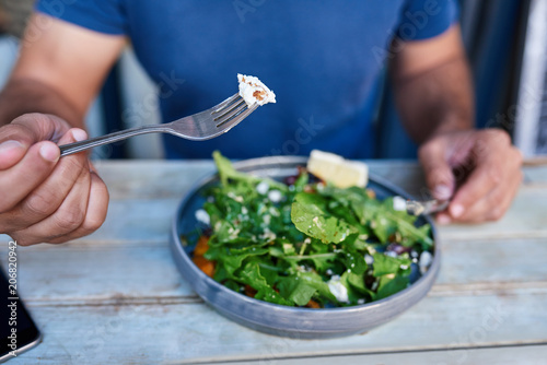 Fotografia Man eating delicious salad at a rustic wooden table