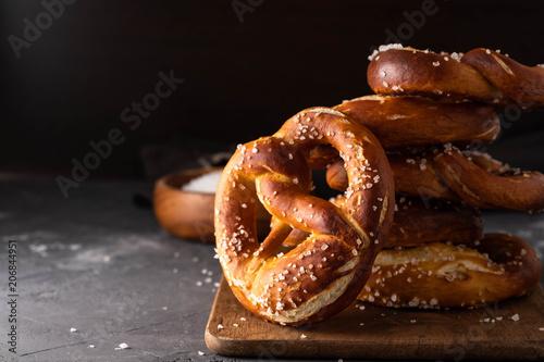Fototapeta Freshly baked homemade soft pretzel with salt on rustic table