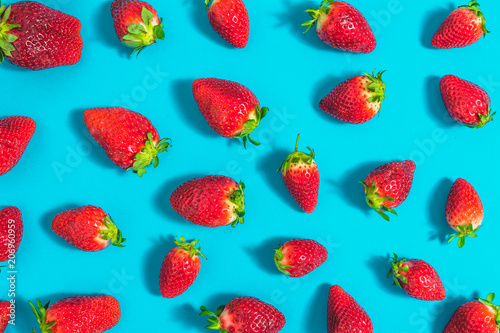 Red pattern of strawberries on blue background, fresh strawberry, flat lay, o...