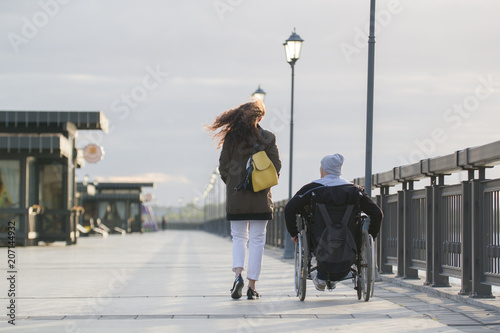 Leinwand Poster Rear view of young woman walking with disabled man in wheelchair on the quay