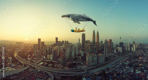 Photo Whale floats in the sky and carrying a plane with two young little sister